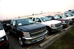 Photo - Chevrolet Silverado pickup trucks are seen on a dealer's lot in Troy, Mich., Monday, Dec. 17, 2012. General Motors is offering generous deals to clear a growing inventory of Chevy and GMC pickup trucks. Itís matching or beating deals offered by Ford and Chrysler. That, plus low interest rates, sweet lease deals and abundant financing, is good news for truck buyers. (AP Photo/Carlos Osorio)