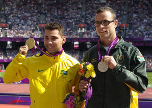 Photo -   Gold medal winner Brazil's Alan Oliveira, left, poses for photographers beside silver medalist South Africa's Oscar Pistorius during after the medal ceremony for the men's 200m T44 category final during the athletics competition at the 2012 Paralympics, Monday, Sept. 3, 2012, in London. Pistorius, who won a legal battle to compete wearing carbon-fiber blades alongside able-bodied runners at the Olympics last month, suggested after the race that Oliveira ran with longer prosthesis than should be allowed. (AP Photo/Raissa Ioussouf)