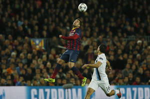Photo - Barcelona's Jordi Alba, left jumps above Manchester City's Sergio Aguero during a Champions League, round of 16, second leg, soccer match between FC Barcelona and Manchester City at the Camp Nou Stadium in Barcelona, Spain, Wednesday March 12, 2014. (AP Photo/Emilio Morenatti)