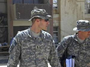 Photo - 1st Lt.  Michael C.  Behenna, left, and his defense attorney Capt. Tom Clark, right, walk in Camp Speicher, a large U.S. base near Tikrit, north of Baghdad, Iraq, Sunday, Sept. 21, 2008.  Behenna is charged with fatally shooting an Iraqi detainee earlier this year and lying about it. His pretrial hearing started Sunday at Camp Speicher. (AP Photo/Vanessa Gera)