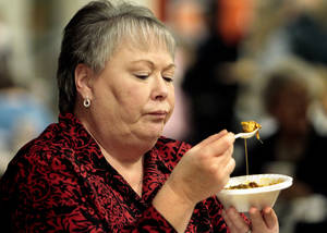 Photo - Kathy LaMar, assistant to the Norman police chief, samples a bowl of chili Thursday at the Police-Fire Chili Supper that raises money for the Cleveland County Christmas Store. PHOTO BY STEVE SISNEY, THE OKLAHOMAN <strong>STEVE SISNEY</strong>
