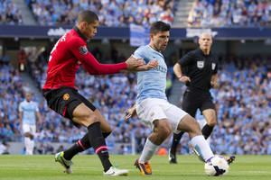 Photo - Manchester City's Sergio Aguero, centre, keeps the ball from Manchester United's Chris Smalling during their English Premier League soccer match at the Etihad Stadium, Manchester, England, Sunday Sept. 22, 2013. (AP Photo/Jon Super)