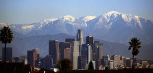 Photo - Snow-covered San Gabriel mountains rise behind downtown Los Angeles Wednesday, Dec. 19, 2012. Winds that tore down trees and power lines eased Wednesday in Southern California but chilly weather remained and the cold was expected to deepen, with sub-freezing temperatures possible. (AP Photo/Nick Ut)