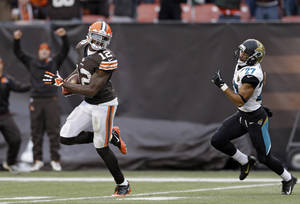 Photo - Cleveland Browns wide receiver Josh Gordon (12) outruns Jacksonville Jaguars cornerback Dwayne Gratz (27) on a 95-yard touchdown reception in the fourth quarter of an NFL football game on Sunday, Dec. 1, 2013, in Cleveland. (AP Photo/Tony Dejak)