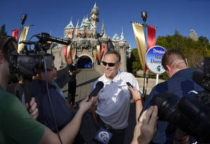 Photo - Michigan State coach Mark Dantonio speaks to reporters in front of Sleeping Beauty Castle during a visit to Disneyland, Thursday, Dec. 26, 2013, in Anaheim, Calif. Stanford and Michigan State are scheduled to meet in the Rose Bowl on New Year's Day. (AP Photo/Mark J. Terrill)
