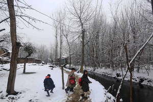 Photo - Kashmiri Muslim children walk on snow covered roads after fresh snowfall, in the outskirts of Srinagar, India, Thursday, Jan. 9, 2014. Traffic on the 300 kilometers (186 miles) long Jammu-Srinagar national highway has been suspended due to heavy snowfall, according to news reports. (AP Photo/Dar Yasin)