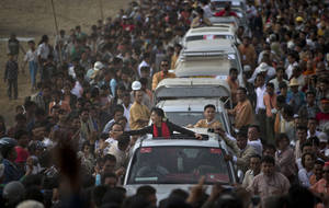 photo - Opposition leader Aung San Suu Kyi reaches for supporters as she leaves after a public meeting close to Letpadaung mine in Monywa, northwestern Myanmar, Friday, Nov. 30, 2012. Suu Kyi is urging a negotiated resolution to protests over a military-backed copper mine in northwestern Myanmar after the government's biggest crackdown on demonstrators since reformist President Thein Sein took office last year. (AP Photo/Gemunu Amarasinghe)