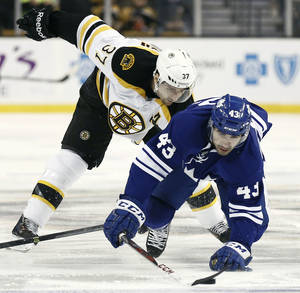 Photo - Toronto Maple Leafs' Nazem Kadri (43) reaches for the puck past Boston Bruins' Patrice Bergeron during the first period of an NHL hockey game in Boston on Monday, March 25, 2013. (AP Photo/Winslow Townson)