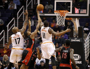 Photo - Phoenix Suns' Markieff Morris (11) tips in a basket between Toronto Raptors' Kyle Lowry (7) and Amir Johnson (15) as Suns' P.J. Tucker (17) looks to rebound during the second half of an NBA basketball game on Friday, Dec. 6, 2013, in Phoenix. (AP Photo/Ralph Freso)