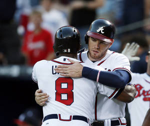 Photo - Atlanta Braves left fielder Justin Upton (8) gets a hug from first baseman Freddie Freeman (5) after hitting a three-run home run in the first inning of a baseball game against the Cincinnati Reds Friday, April , 25, 2014 in Atlanta. (AP Photo/John Bazemore)