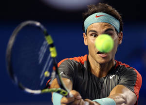 Photo - Rafael Nadal of Spain makes a backhand return to Bernard Tomic of Australia during their first round match at the Australian Open tennis championship in Melbourne, Australia, Tuesday, Jan. 14, 2014.(AP Photo/Rick Rycroft)