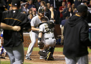 Photo - Pittsburgh Pirates relief pitcher Jason Grilli, left, picks up catcher Russell Martin after a baseball game and Pirates 2-1 win over the Chicago Cubs Monday, Sept. 23, 2013, in Chicago. (AP Photo/Charles Rex Arbogast)