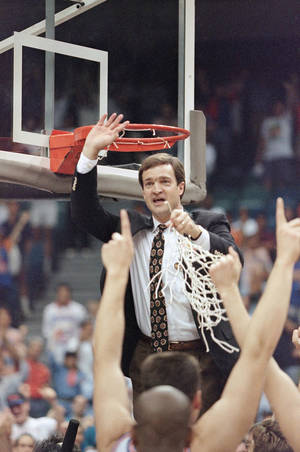 Photo - Florida coach Lon Kruger gets a piece of the net after his Florida Gators defeated Boston College in the NCAA East Regional Finals in Miami, Sunday, March 27, 1994 by a score of 74-66. (AP Photo/Hans Deryk)