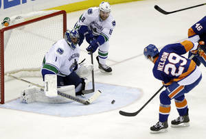 Photo - Vancouver Canucks goalie Roberto Luongo (1) and Ryan Stanton (18) defend the goal as New York Islanders' Brock Nelson (29) shoots the puck during the second period of an NHL hockey game Tuesday, Oct. 22, 2013 in Uniondale, N.Y. (AP Photo/Frank Franklin II)
