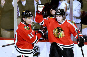 Photo - Chicago Blackhawks left wing Patrick Sharp, left, and right wing Patrick Kane celebrate Kane's goal during the third period of an NHL hockey game against the Minnesota Wild, Tuesday, March 5, 2013 in Chicago. The Blackhawks won 5-3.  (AP Photo/Brian Kersey)