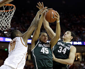 Photo - Michigan State's Denzel Valentine (45) pulls in a rebound between teammate Gavin Schilling (34) and Texas' Jonathan Holmes (10) during the first half of an NCAA college basketball game, Saturday, Dec. 21, 2013, in Austin, Texas. (AP Photo/Eric Gay)