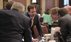 Photo - Speaker of the House Jase Boger, R-Marshall, talks over Detroit bailout bills with a huddle of Republicans Thursday, May 22, 2014 on the floor of the Michigan House of Representatives. The Michigan House has approved Detroit bankruptcy legislation that commits $195 million in state money to prevent deeper cuts in retiree pensions and the sale of city-owned art. The House voted 74-36 Thursday to spend money to match contributions from foundations and the Detroit Institute of Arts. Eleven bankruptcy-related bills cleared the Republican-led chamber and go to the Senate. (AP Photo/Detroit News, Dale G. Young)  DETROIT FREE PRESS OUT; HUFFINGTON POST OUT