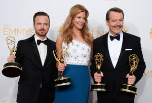"""Photo - Aaron Paul, left, poses with the award for outstanding supporting actor in a drama series, with Anna Gunn, center, with the award for outstanding supporting actress in a drama series, and Bryan Cranston with the awards for outstanding lead actor in a drama series and outstanding drama series for """"Breaking Bad"""" in the press room at the 66th Annual Primetime Emmy Awards at the Nokia Theatre L.A. Live on Monday, Aug. 25, 2014, in Los Angeles. (Photo by Jordan Strauss/Invision/AP)"""