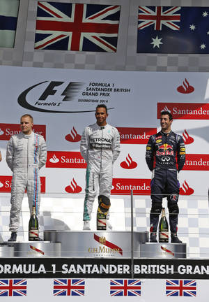 Photo - Britain's Lewis Hamilton of Mercedes centre, who won the race, Finland's Valtteri Bottas of Williams, left, who finished second, and Australia's Daniel Ricciardo, right,  of Red Bull finished third stand n the podium after winning the British Formula One Grand Prix at Silverstone circuit, Silverstone, England, Sunday, July 6, 2014. (AP Photo/Lefteris Pitarakis)
