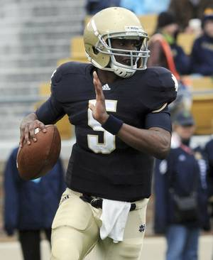 Photo - FILE - In this April 16, 2011, file photo, Notre Dame quarterback Everett Golson sprints out of the pocket during the first half of a spring NCAA college football game in South Bend, Ind. A Notre Dame spokesman says Golson is no longer enrolled at the school. (AP Photo/Joe Raymond, File)