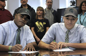 Photo - Cathedral Preparatory School seniors Delton Williams, left, and Damion Terry, attend a ceremonial letter-of-intent signing at the school in Erie, Pa., on Wednesday, Feb. 6, 2013. Earlier in the day, they signed their actual letters of intent to attend and play football at Michigan State. (AP Photo/Erie Times-News, Christopher Millette) MAGS OUT, TV OUT
