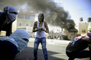 Photo - A Palestinian holds a Molotov cocktail during clashes with Israeli border police in Jerusalem on Wednesday, July 2, 2014. The suspected abduction of an Arab teen followed by the discovery of a body in Jerusalem on Wednesday ignited clashes between Israeli police and stone-throwing Palestinians, who saw it as a revenge attack for the killing of three Israeli teens in the West Bank. (AP Photo/Mahmoud Illean)