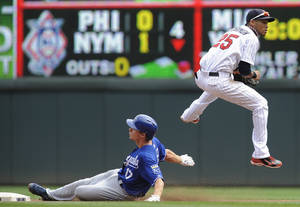 Photo - Minnesota Twins shortstop Pedro Florimon, right, jumps to avoid the slide of Kansas City Royals' Chris Getz, left, after getting the force at second on a double play during the fourth inning of a baseball game, Thursday, Aug. 29, 2013, in Minneapolis. (AP Photo/Tom Olmscheid)