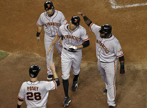 photo -   San Francisco Giants' Hunter Pence, center, is greeted by teammates Buster Posey (28), Marco Scutaro, top left, and Pablo Sandoval, right, after hitting a grand slam against the Arizona Diamondbacks during the third inning of a baseball game on Friday, Sept. 14, 2012, in Phoenix. (AP Photo/Matt York)