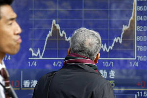 Photo - A man looks at an electronic stock board of a securities firm in Tokyo, Thursday, Jan. 10, 2013. A positive start to U.S. corporate earnings season helped boost Asian stock markets Thursday. (AP Photo/Koji Sasahara)