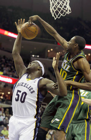 Photo - Utah Jazz's Jeremy Evans, right, slaps the ball away from Memphis Grizzlies' Zach Randolph (50) in the first half of an NBA basketball game in Memphis, Tenn., Monday, Dec. 23, 2013. (AP Photo/Danny Johnston)