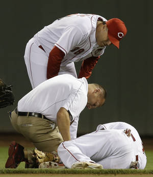 Photo - Cincinnati Reds second baseman Brandon Phillips is checked by trainer Steve Bauman, center, and manager Bryan Price, top, after Phillips was injured in the eighth inning of a baseball game against the Chicago Cubs, Wednesday, July 9, 2014, in Cincinnati. Phillips was taken out of the game won by Cincinnati 4-1. (AP Photo/Al Behrman)
