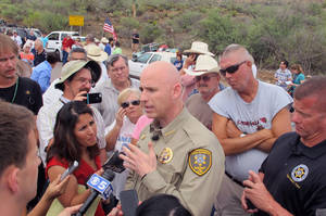 Photo - Pinal County Sheriff Paul Babeau speaks to the media as protesters gather near the entrance to juvenile facility in an effort to stop a bus load of Central American immigrant children from being delivered to the facility, Tuesday, July 15, 2014, in Oracle, Ariz. Federal officials delayed the bus with no details on whether the children will arrive or not. (AP Photo/Brian Skoloff)