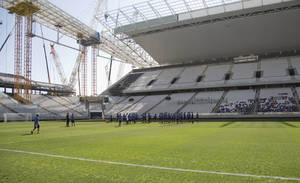 Photo - Brazilian club Corinthians soccer players practice at the Itaquerao, the stadium that will host the World Cup opener in less than three months in Sao Paulo, Brazil, Saturday, March 15, 2014. The Itaquerao was one of the six stadiums that were supposed to be finished by the end of 2013, but a crane collapse that killed two workers in November caused significant delays to the venue where Brazil will play Croatia on June 12. The stadium is not expected to be ready before mid-April. (AP Photo/Andre Penner)