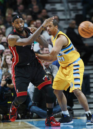 Photo - Miami Heat forward LeBron James, left, passes ball around Denver Nuggets guard Andre Miller in the fourth quarter of the Heat's 97-94 victory in an NBA basketball game in Denver on Monday, Dec. 30, 2013. (AP Photo/David Zalubowski)