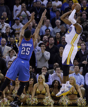 Photo - Golden State Warriors' Andre Iguodala, right, shoots the game-winning shot over Oklahoma City Thunder's Thabo Sefolosha (25) during the second half of an NBA basketball game Thursday, Nov. 14, 2013, in Oakland, Calif. (AP Photo/Ben Margot)