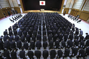 Photo - New ministry workers bow during a welcome ceremony for them at Defense Ministry in Tokyo, Tuesday, April 1, 2014. Japan relaxed a decades-old ban on military-related exports Tuesday in a bid to expand joint arms development with allies and equipment sales to Southeast Asia and elsewhere. (AP Photo/Eugene Hoshiko)