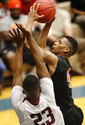 photo - Douglass player DeAngelo Smith drives toward the basket against Muldrow's Nate Hamilton during first round games of Class 4A basketball state tournament in the Lyle Boren Activity Center at Choctaw High School on Thursday,  March 7, 2013.  Photo by Jim Beckel, The Oklahoman