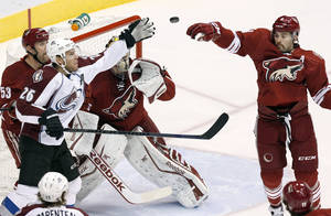 Photo - Colorado Avalanche's Paul Stastny (26) and Phoenix Coyotes' Keith Yandle, right, reach out to catch the puck as Coyotes' Derek Morris (53) and Mike Smith stand by during the first period of an NHL hockey game Thursday, Nov. 21, 2013, in Glendale, Ariz. (AP Photo/Ross D. Franklin)