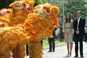 Photo -   Britain's Prince William and his wife Kate, the Duke and Duchess of Cambridge, are welcomed by a lion dance performance during their visit to Strathmore Green, a precinct in Queenstown, a residential district of Singapore on Wednesday, Sept. 12, 2012. Britain's royal couple are on a nine-day tour of the Far East and South Pacific. (AP Photo/Nicolas Asfouri, Pool)