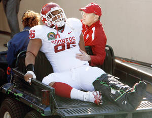 Photo - Oklahoma's Adrian Taylor is carted off the field Thursday. Photo by Chris Landsberger, The Oklahoman