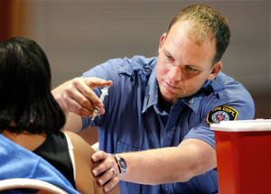 Photo -  Oklahoma City firefighter Brian Foreman injects a woman with H1N1 vaccine at the Centennial Building at State Fair Park Tuesday morning,  Nov. 24, 2009.   Photo by Jim Beckel, The Oklahoman