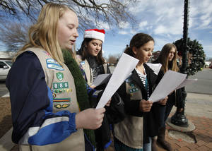 Photo - Girl Scouts, from left, Rachel Barrett, Eleni Tsaras, Brooklyn Phillips and Emma Harper sing Christmas carols in downtown Edmond.  PHOTO BY PAUL HELLSTERN, THE OKLAHOMAN