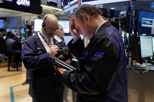 Photo - Trader Randy Beller, right,  works on the floor of the New York Stock Exchange, Monday, April 7, 2014.  Stocks are starting out the week the same way they ended the last one,  down. (AP Photo/Richard Drew)