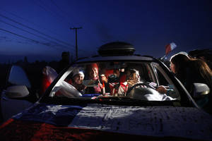 Photo - Chile soccer fans are illuminated by lights from a local TV station as they are interviewed in their car just before departing with a caravan for the World Cup in Brazil, from Santiago, Chile, early Friday June 6, 2014. Held every four years, the World Cup hasn't been in the Americas since 1994, when the United States played host. For many, this is a once in a lifetime chance to cheer their national teams in person. (AP Photo/Luis Hidalgo)