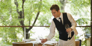 Photo - Waiter placing glasses on table in restaurant