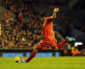 Photo - Liverpool's Luis Suarez scores the fourth goal of the game from a free kick during their English Premier League soccer match against Norwich City at Anfield in Liverpool, England, Wednesday Dec. 4, 2013. (AP Photo/Clint Hughes)