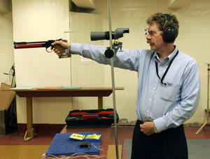 Photo - FILE--In this Feb. 21, 2007 file photo, Bruce Martindale takes aim as he competes in a weekly air gun league in Troy, N.Y. Martindale, who normally uses a .22-caliber, has cut back on practice because ammunition is in short supply. (AP Photo/Mike Groll, File)