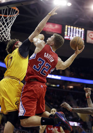 Photo - Los Angeles Clippers' Blake Griffin (32) jumps to the basket against Cleveland Cavaliers' Anderson Varejao (17), from Brazil, during the first quarter of an NBA basketball game on Saturday, Dec. 7, 2013, in Cleveland. (AP Photo/Tony Dejak)