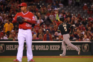Photo - Oakland Athletics' John Jaso, right, rounds third after hitting two-run home run as Los Angeles Angels relief pitcher Ernesto Frieri looks on during the ninth inning of a baseball game, Monday, April 14, 2014, in Anaheim.  (AP Photo/Mark J. Terrill)