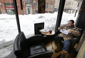 Photo - Matt Church enjoys his breakfast at a coffee shop in downtown Haverhill, Mass., Monday, Feb. 11, 2013. Beleaguered Massachusetts residents returned to work on Monday for the first time since the weekend blizzard, crawling along narrow snow-covered secondary roads and being greeted by a new wintry mix of sleet and freezing rain. (AP Photo/Elise Amendola)